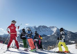 The ski instructor from the Carezza Skischool is teaching the kids about the Dolomites mountain range during Kids Ski Lessons (from 4 years) - Advanced.