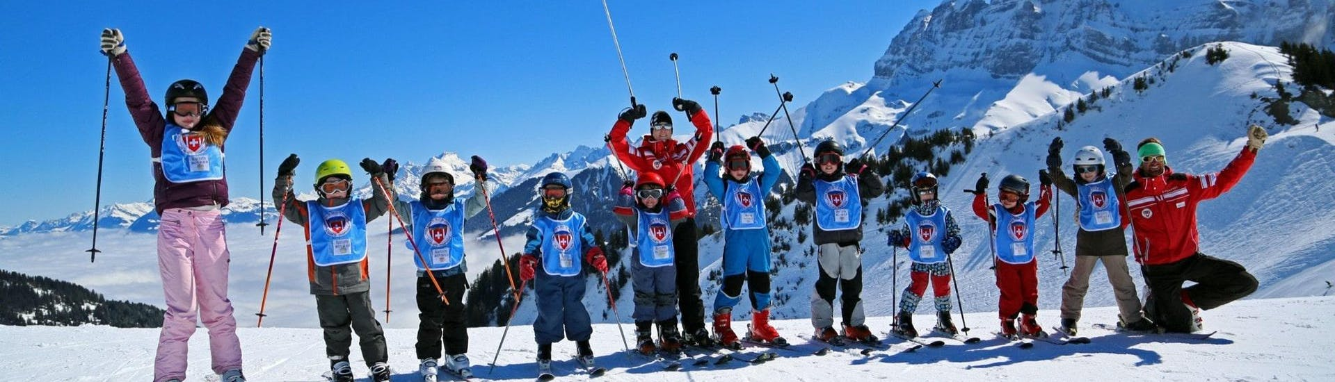 Kids are standing next to one another with their ski poles in the air during their Kids Ski Lessons (from 4 years) - All Levels with the Swiss Ski School Les Crosets-Champoussin.
