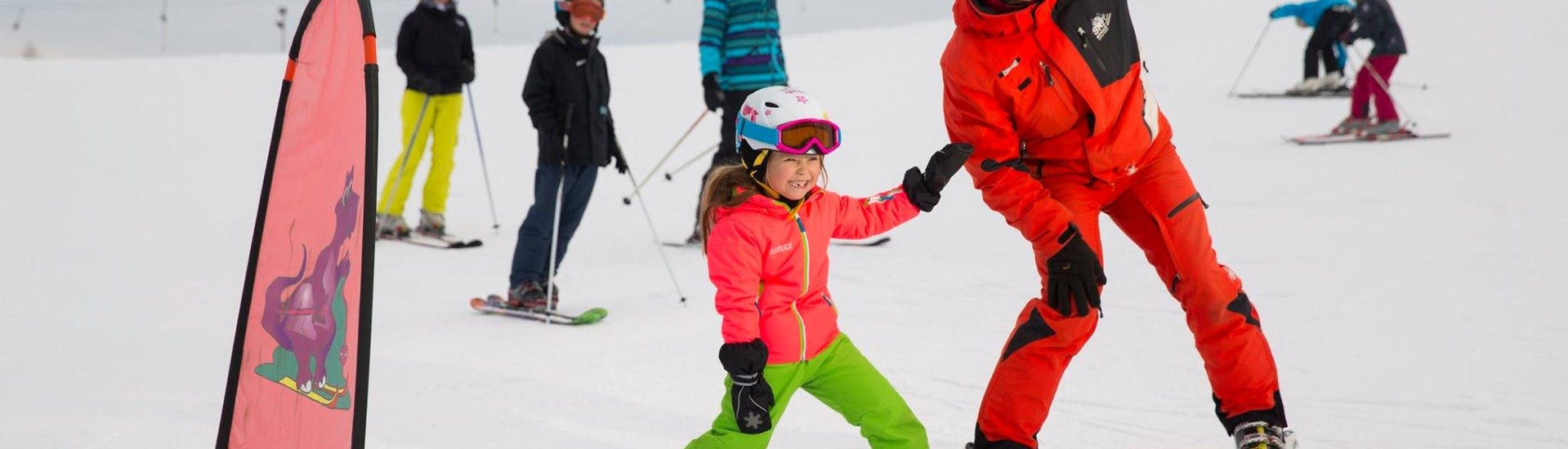 The ski instructor of Skischule Zahmer Kaiser teaches a kid how to ski during the kids ski lesson from 5 years for beginners.