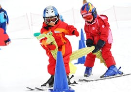 Two young children are practicing their first turns on skis during their Kids Ski Lessons (from 5 y.) for First Timers with Schischule Hochgurgl.