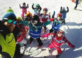 A group of kids with their instructor from the ski school Prosneige Méribel is smiling to the camera just before their Kids Ski Lessons (from 5 y.) - Equipment included.