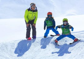 Two young skiers are learning to ski with the encouragement of their instructor from the ski school Prosneige Méribel during their Kids Ski Lessons (from 5 yo) - All Levels & Ages.