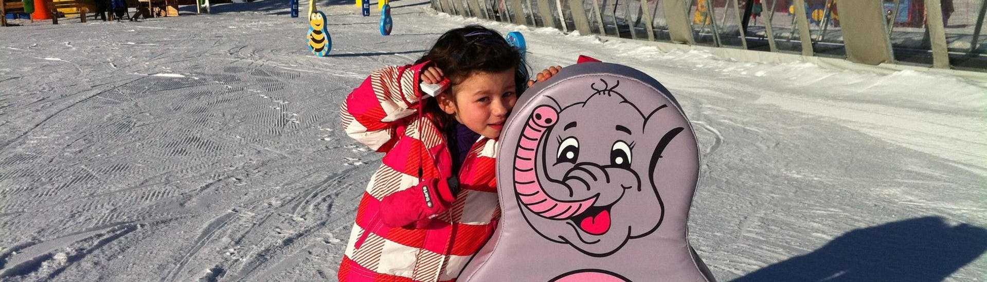 A little girl is posing for a photo with a cute elephant during the Kids Ski Lessons (from 6 years) - Advanced organised by the ski school Skischule Arena in Zell am Ziller.