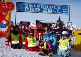 A group of young skiers and their ski instructor from the ski school Skischule Pro Zell in Zell am Ziller are playing around in the protected play area for children during their Kids Ski Lessons (from 6 years) - Advanced.