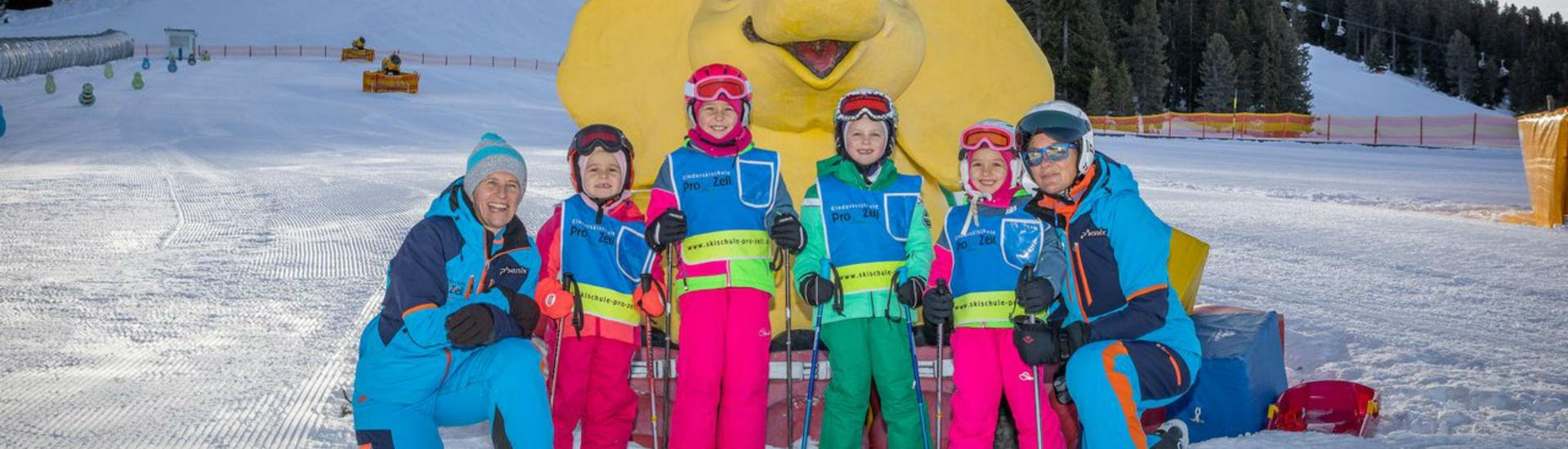 A group of children and their two ski instructors from the ski school Skischule Pro Zell in Zell am Ziller are posing for a photo in the Kinderland area during their Kids Ski Lessons (from 6 years) - Advanced .
