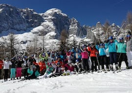 The Kids Ski Lessons (from 9 y.) - Full Day - Advanced are over and the participants in the final race are on the podium, the ski school teacher of the Scuola Italiana di Sci Civetta celebrates with them.