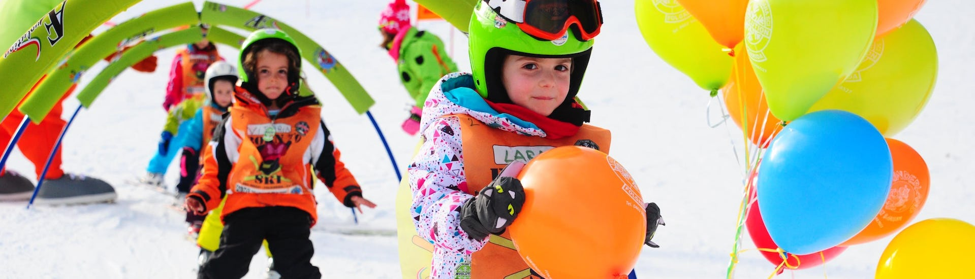 """The Kids Ski Lessons """"Full Day"""" (4-8 years) - Christmas of the AEvolution Folgarida Ski School are taking place in the school field; the child overcame the obstacles and deserved a balloon."""