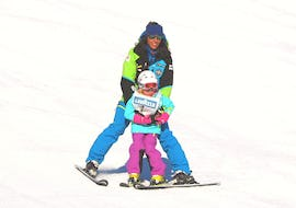 A ski instructor helps a little girl to get down a slope in Livigno for the first time during the Kids Ski Lessons Half Day (3-4 y.) - Beginner of the ski school Scuola di Sci e Snowboard Livigno Italy.