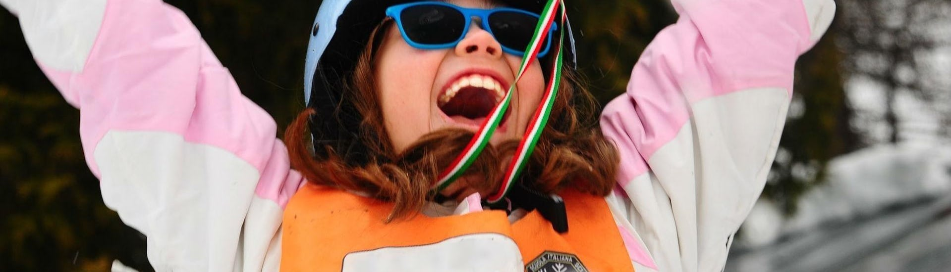 """Kids Ski Lessons """"Half Day"""" (3-4 years) - Beginner Ski School AEvolution Folgarida are at the end, a little girl has been awarded and celebrates on the podium."""