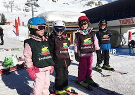 "Four young skiers are learning how to ski in the safe environment of the Kids Club of the ski school Evolution 2 Tignes during their Kids Ski Lessons ""Kids Club"" (3-5 years) - Morning."