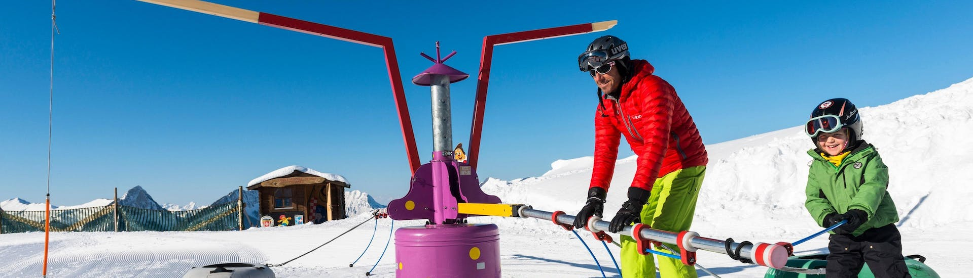"""A kid is learning how to take the chairlift with the help of a ski instructor from the swiss ski school Charmey during their Ski Lessons """"Kids Snow Garden"""" (3-5 years) - 4 lessons."""