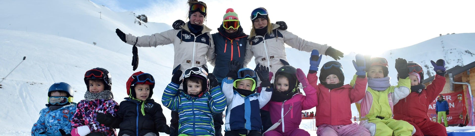 """Kids are sitting with their ski instructors from the ski school ESI Valfréjus in the middle of the kindergarten during their Kids Ski Lessons """"Kindergarten"""" (3-5 years)."""
