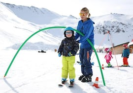 "A young skier is learning how to ski in the safety of a snowgarden during their Kids Ski Lessons ""Kindergarten"" (3-5 years) with the ski school ESI Valfréjus."