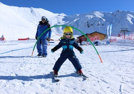 "A young skier is learning how to ski in the safety of a snowgarden during their Kids Ski Lessons ""Kindergarten"" (3-5 years) - Holidays with the ski school ESI Valfréjus."