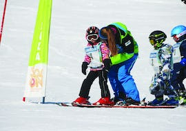 "A ski instructor encourages children during the Kids Ski Lessons ""Low Season"" (5-12 y.) - All Levels of the ski school Scuola di Sci e Snowboard Livigno Italy."