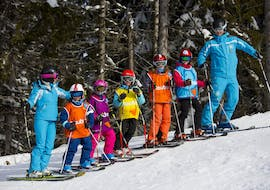 """Young skiers are standing in line between their ski instructors from the ski school ESI Font Romeu during their Kids Ski Lessons """"Max 6"""" (6-12 years) - Low Season."""