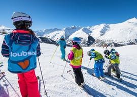 The ski instructor from the ski school ESI Ski Family in Risoul is giving his final instructions before the skiers head to the slopes for their Kids Ski Lessons (5-13 y.) - February - Morning.