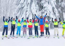 In the Kids Ski Lessons (from 5 years) - Advanced organized by the ski school Neue Skischule Winterberg the participants pose for a photo in front of the snowy landscape together with their ski instructor.