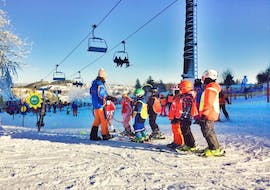 During the Kids Ski Lessons (from 5 years) - Beginners with the ski school Neue Skischule Winterberg, a ski instructor is explaining a new exercise to a group of young skiers.