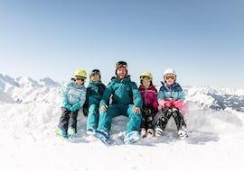 """Eine Gruppe von Kindern hat Spaß im Kinder Skikurs """"NTC Kids Academy"""" (6 Jahre) - Alle Levels mit einem freundlichen Skilehrer der Skischule NTC Skischule Oberstdorf."""