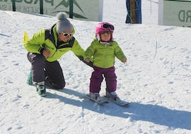 "A young child is learning to ski with the help of a ski instructor from the ski school Prosneige Val Thorens & Les Menuires during Kids Ski Lessons ""Petits Ours"" (3-4 years)."