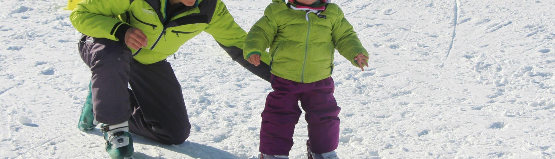 """A young child is learning to ski with the help of a ski instructor from the ski school Prosneige Val Thorens & Les Menuires during Kids Ski Lessons """"Petits Ours"""" (3-4 years)."""
