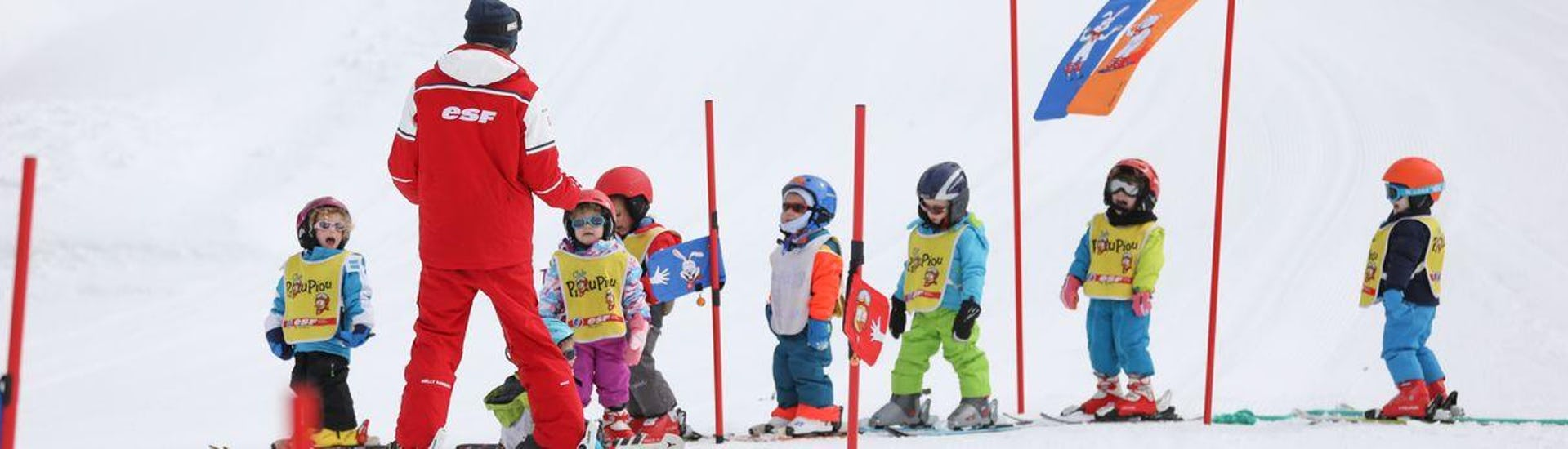 "Kids are standing in line learning to find their balance on skis during their Kids Ski Lessons ""Piou-Piou"" (3-5 y.) - February - Morning with the ski school ESF du Dévoluy."