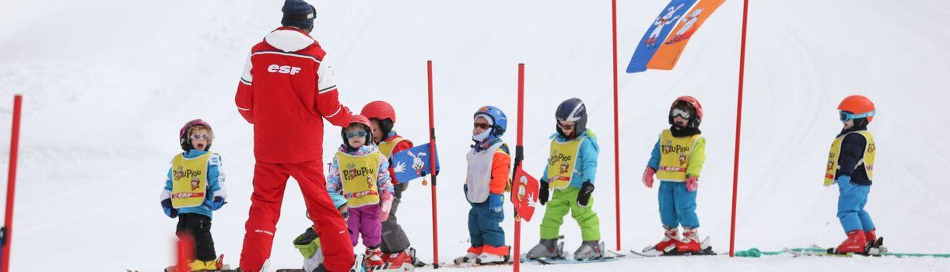 """Kids are standing in line learning to find their balance on skis during their Kids Ski Lessons """"Piou-Piou"""" (3-5 y.) - February - Morning with the ski school ESF du Dévoluy."""