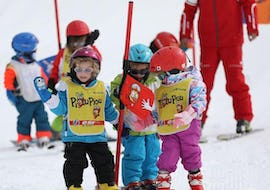 "Kids are standing in the kindergarden playing games helping them to learn to ski during their Kids Ski Lessons ""Piou-Piou"" (3-5 y.) - February - Morning with the ski school ESF du Dévoluy."