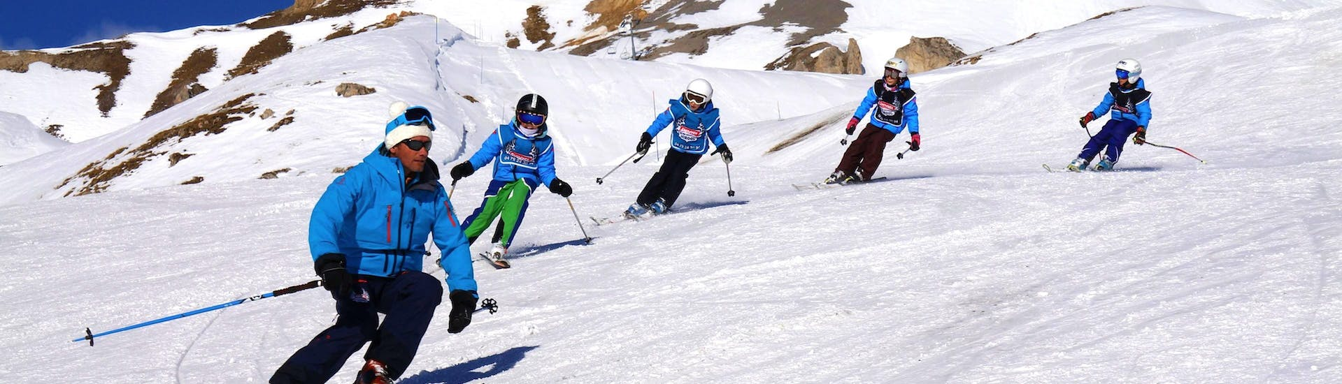 """Young skiers are following their instructor from the ski school Snocool on a snowy slope during theirKids Ski Lessons """"Pop 6"""" (10-17 years) - Advanced."""