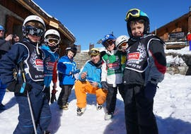 "Young skiers with their ski instructor from the ski school Snocool are smiling to the camera before their Kids Ski Lessons ""Pop 6"" (10-17 years) - Advanced."