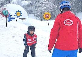 Un moniteur de ski enseigne les bases du ski à un jeune skieur pendant son Cours de ski pour Enfants (4-8 ans) - Tous niveaux avec l'école de ski Schneesportschule Thoma.