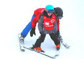 """Pendant le Cours de ski pour Enfants """"Tout-en-un"""" (4-8 ans) avec l'école de ski Schneesportschule Thoma, un moniteur de ski aide un jeune skieur à maîtriser la technique du chasse-neige."""