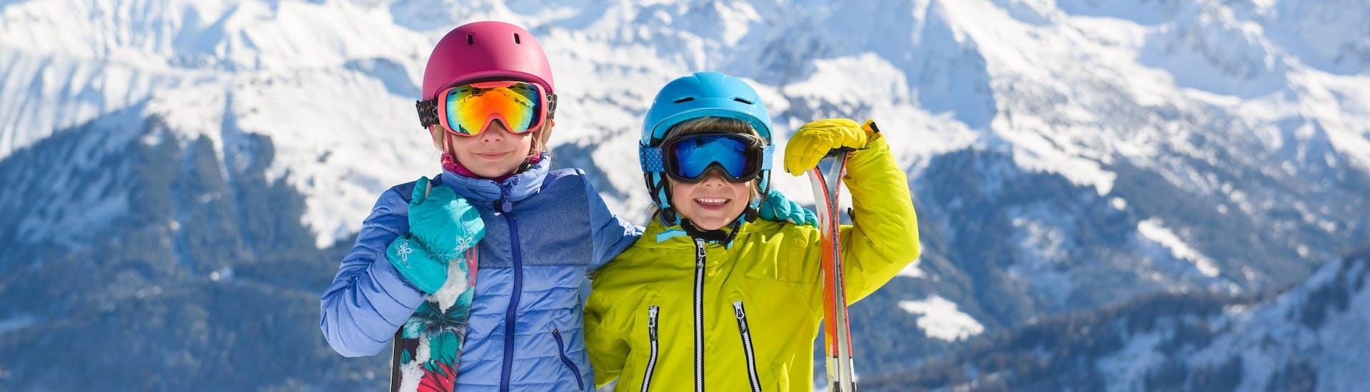 Twee kinderen in complete ski uitrusting glimlachen voor de camera terwijl ze zich voorbereiden op hun kinderskilessen boven op de berg.