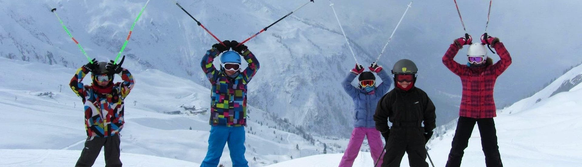 Kids are standing at the top of the mountain with their ski poles up in the air during their Kids Ski Lessons (5-12 years) - Beginner with the ski school ESF Chamonix.