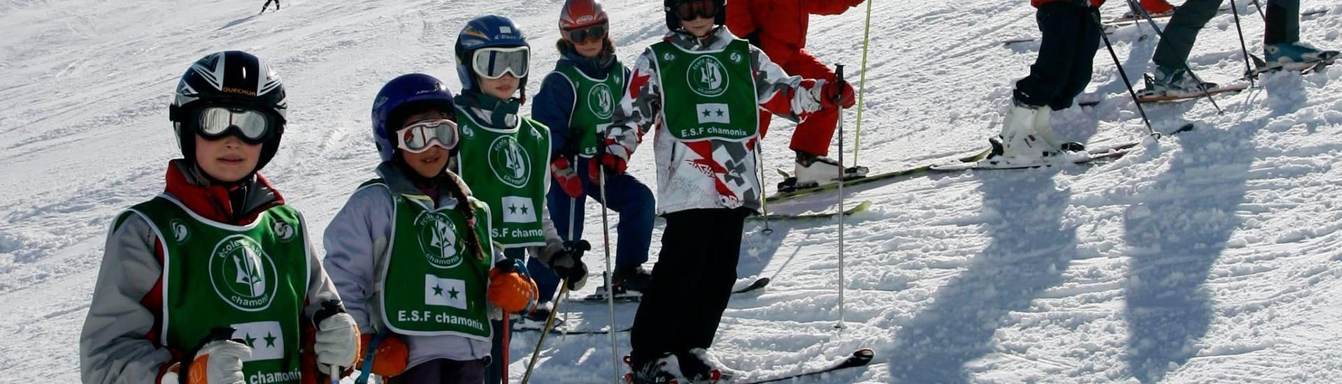 Skiers are standing in the middle of the slope with their instructor from the ski school ESF Chamonix during their Kids Ski Lessons (8-12 years) - Holiday - Advanced.