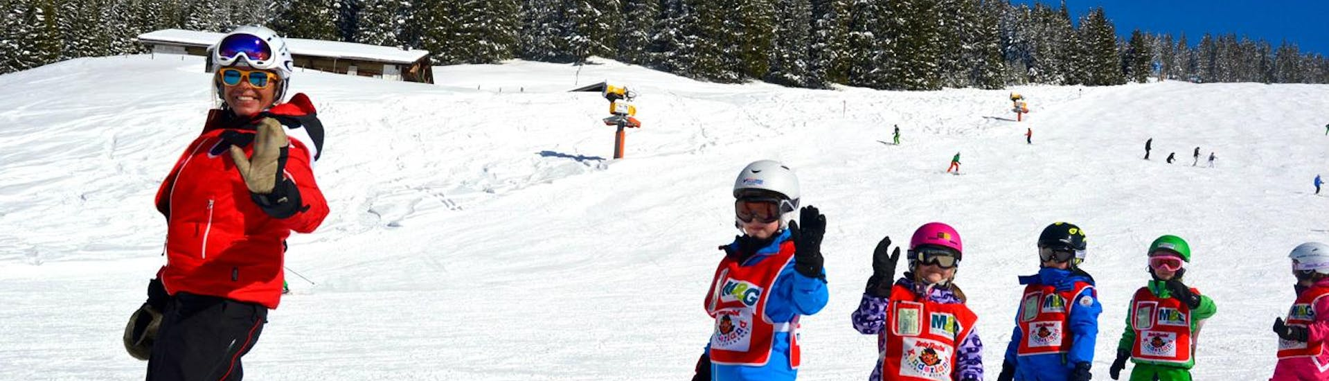 A ski instructor and her group of happy children are waving at the camera as they practice skiing during the Kids Ski Lessons (from 3 years) - All Levels with Skischule Kitzbühel Rote Teufel.