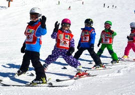 Fröhliche Kinder winken beim Kinder Skikurs (ab 3 Jahren) - Alle Levels mit der Skischule Kitzbühel Rote Teufel in die Kamera.