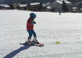 "A young participant of the Kids Ski Lessons ""Las Muntanialas"" (4-17 years) - All-in-One with Skischule Monntains is practicing the first turns on the slopes."