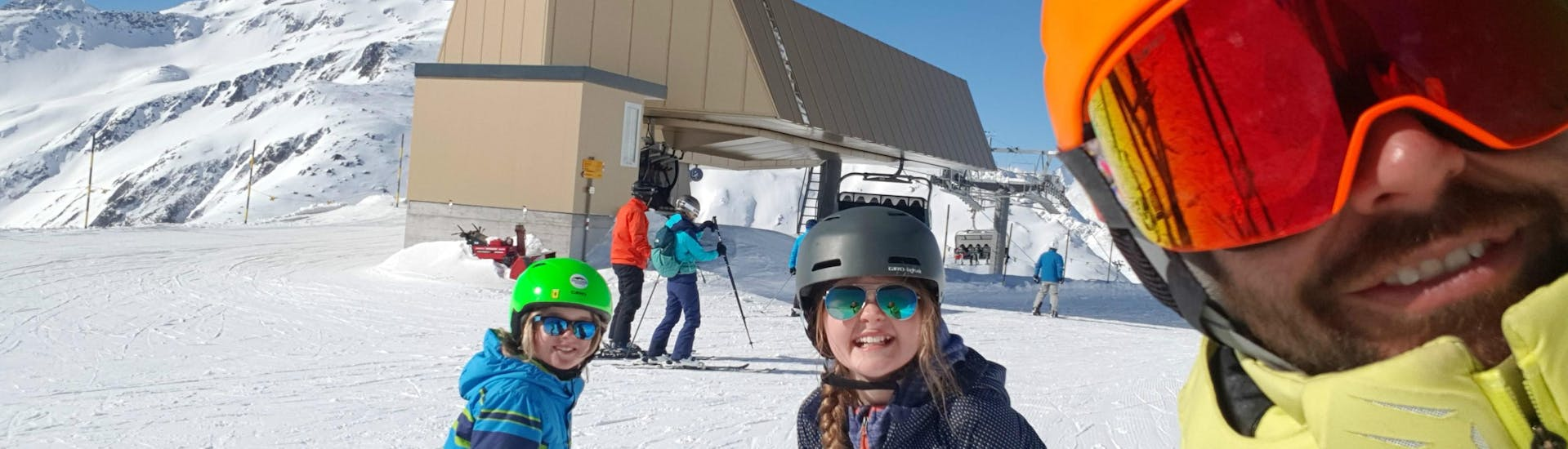 """Two participants of the Kids Ski Lessons """"Ils Camutschs"""" (4-17 years) are posing for a picture with their ski instructor from Skischule Monntains."""