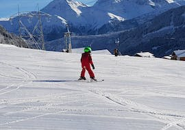 A young child is taking their first steps on skis during the Private Ski Lessons for Kids (from 3 years) - All Levels with Skischule Monntains.