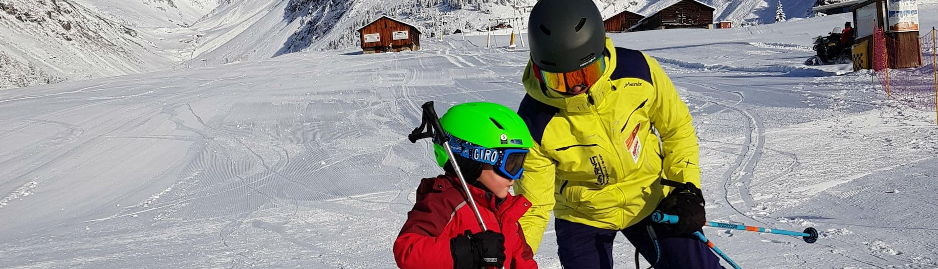 """A ski instructor from Skischule Mountains is helping a participant of the Kids Ski Lessons """"Las Lieurs"""" (4-17 years)."""