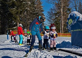 A ski instructor from Skischule Steibis is helping two children on the magic carpet during their Kids Ski Lessons (4-15 years) - Morning - First Timer.