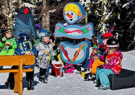 """Children taking a break with a healthy snack and warm tea during their Kids Ski Lessons """"Zimi's Snow Adventure"""" (2.5-4 years) with Skischule Steibis."""