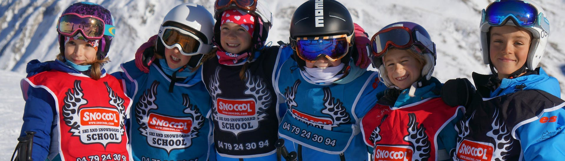 "A group of young skiers are standing in line while smiling at the camera in front of a snowy mountain during their Kids Ski Lessons ""Small Group"" (5-12 years) - All Levels with the ski school Snocool."