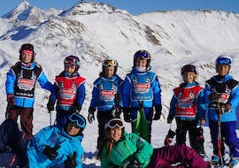 "A group of young skiers are posing for a picture at the top of the slopes with their ski instructors from the ski school Snocool during their Kids Ski Lessons ""Small Group"" (5-12 years) - All Levels."