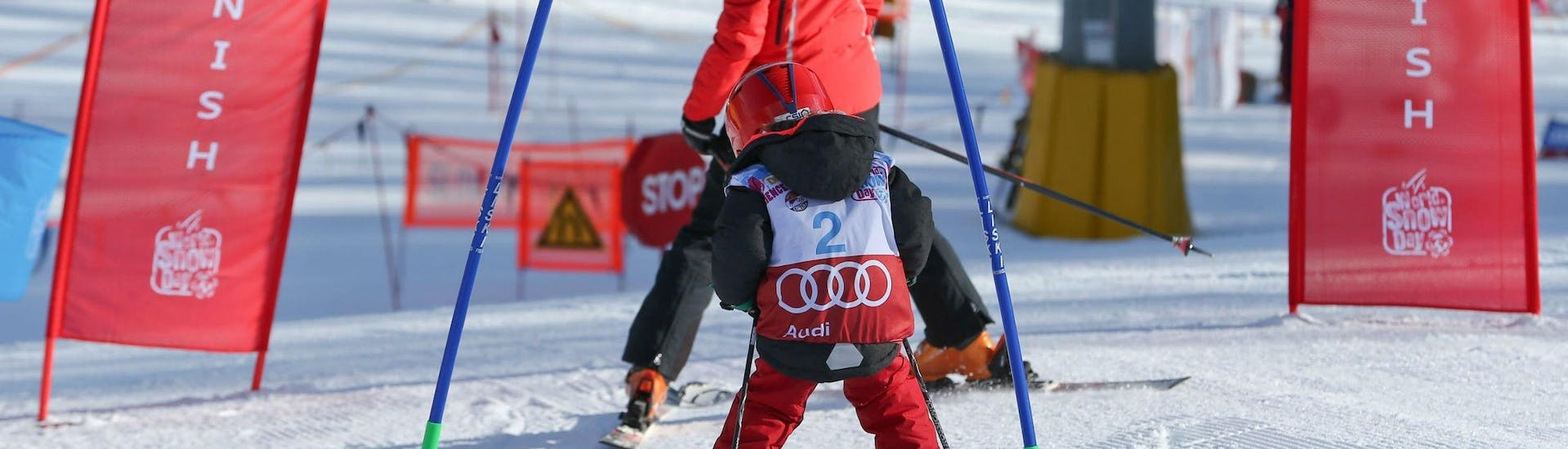 """A young child is practicing its skiing technique on a race course in Cortina d'Ampezzo during one of its Kids Ski Lessons """"Smart"""" (4-12 years) - With Experience organised by the ski school Scuola Sci Cortina."""