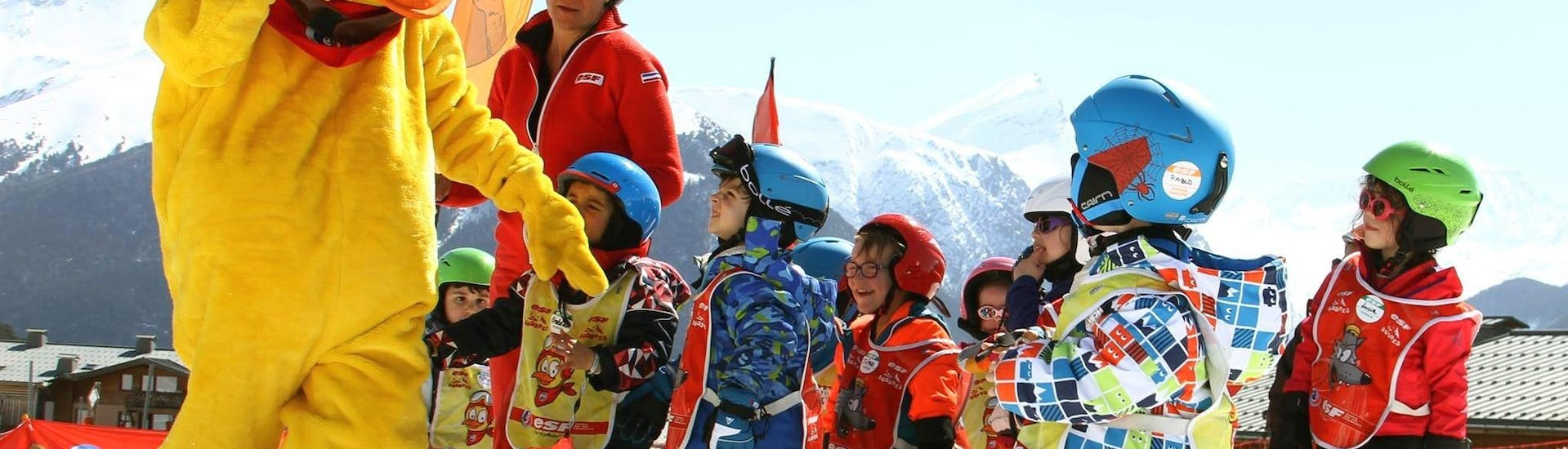 """Kids are happy to learn to ski with the mascot of the ski school ESF Aussois during their Kids Ski Lessons """"Snow school"""" (2½-3 y.)."""