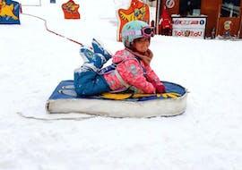 """Un jeune enfant s'amuse sur une luge pendant son Premier Cours de ski Enfants """"École des neiges"""" (2½-3 ans) avec l'école de ski ESF Aussois."""