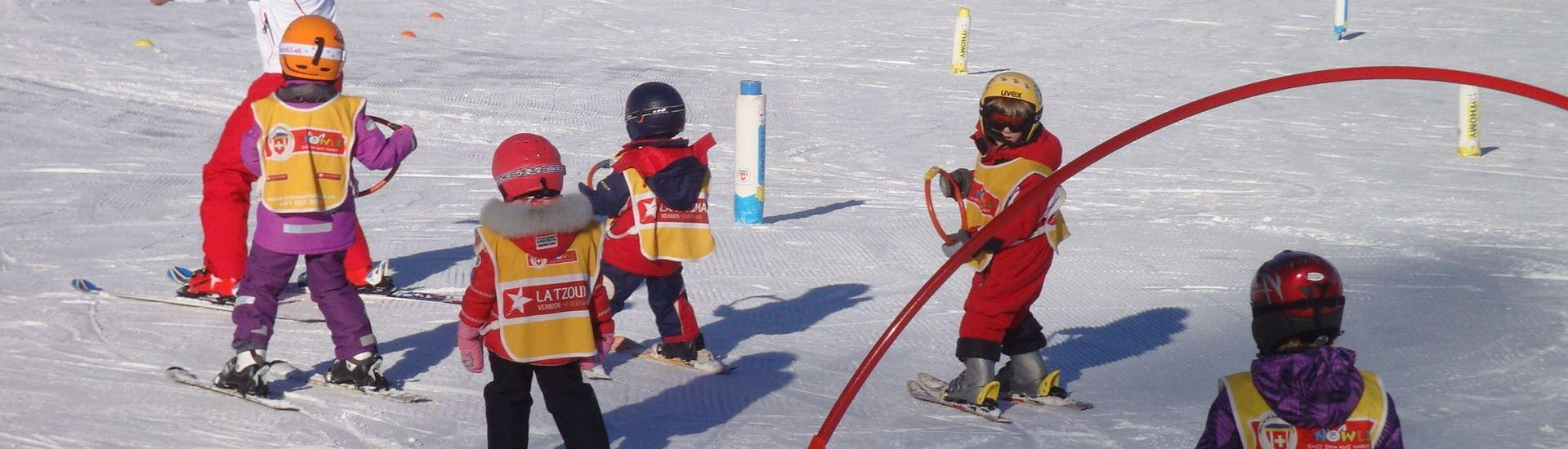 """Kids are learning the basics of skiing thanks to games in the safety of the snowgarden during their Kids Ski Lessons """"Snowgarden"""" (3-6 years) - Morning with the Swiss Ski School La Tzoumaz."""